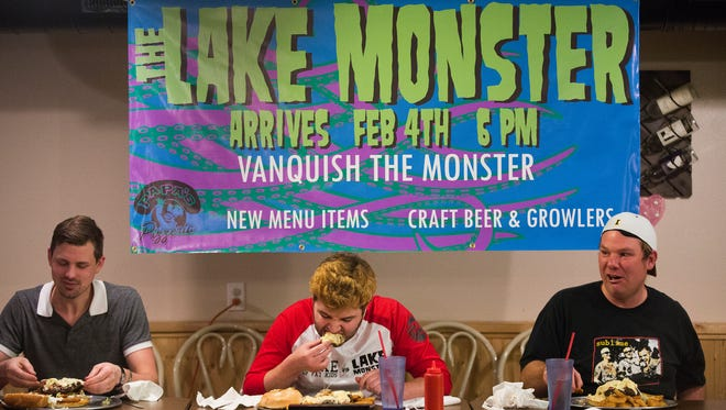 Seth Bass of Windsor Heights, left, Seth Cloe, and Ryan Bales, both of Des Moines, partake in an eating contest at Papa's Pizzeria in Polk City, Thursday, Feb. 4, 2016. They were challenged to eat a new sandwich called the Lake Monster which consists of a pizza, pork tenderloin, four chicken strips, a bacon cheeseburger, mac and cheese sauce, bun, and onion rings. It weighs three pounds ten ounces.