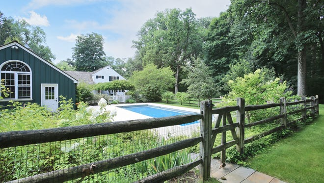 This historic home has a picket fence around it, enclosing the pool and pool house, as well as flower beds and more.