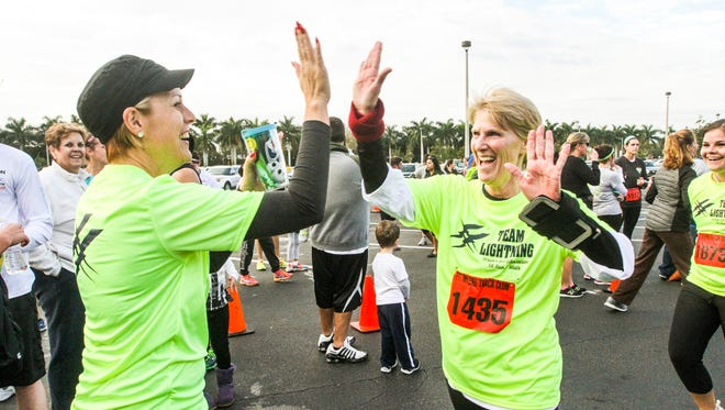 (left) Lehigh Senior High Principal, Jackie Corey, high-fives Robin Walden(center) after Walden finished her run. Elise Leyva comes in for her high-five next.  They were part of Lehigh's Team Lighting. More than 1,000 runners took off through  Florida SouthWestern State College Lee Campus, all for the Foundation for Lee County Public Schools. They held their 5th Annual Strides for Education 5K Run and Walk on Saturday February 6, 2016. The event will raise money for The FoundationÕs Take Stock in Children program.