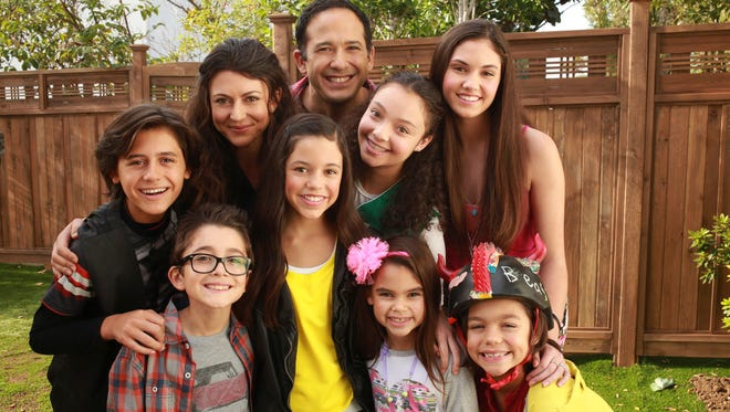 """Jenna Ortega, (standing in the middle wearing a yellow shirt) plays Harley in the Disney show """"Stuck In The Middle"""" and in this photo is surrounded by her TV family."""