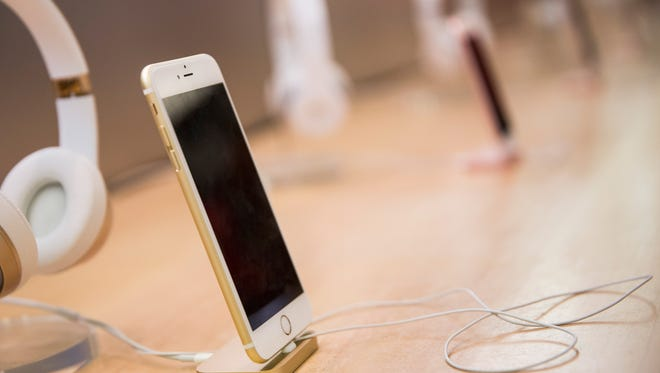An iPhone sits on display inside the Apple store on Fifth Avenue on January 26, 2016 in New York City. This afternoon Apple reported the slowest iPhone earnings since 2007.  (Photo by Andrew Burton/Getty Images) ORG XMIT: 602058287 ORIG FILE ID: 506969642