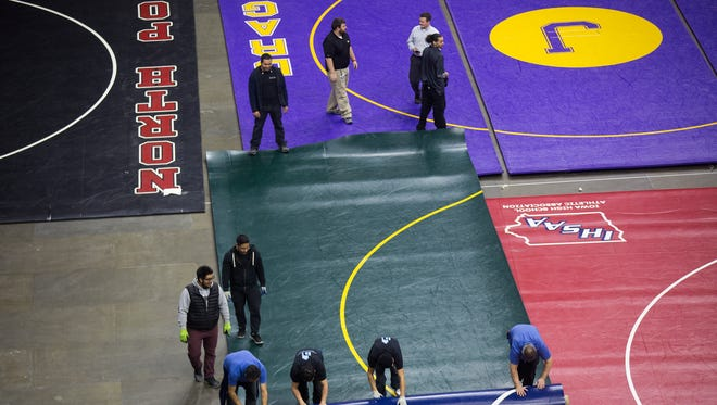 Wrestling mats are unrolled by temp workers in preparation of the state high school wrestling tournament at Wells Fargo Arena in Des Moines, Monday, Feb. 15, 2016. The tournament begins Wednesday and will go thru Saturday.
