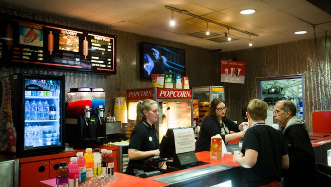 Moviegoers buy popcorn, soda and other refreshments before a Saturday matinee at Village 8 Theatres, which is closing by the end of 2016.