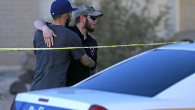 A friend who wished to remain unidentified, left, greets family member Rick Zard outside the home Wednesday, Feb. 24,  2016, where five people died in Phoenix.  Police believe Alex Buckner, 26, killed four members of his own family then set the house on fire on Tuesday.