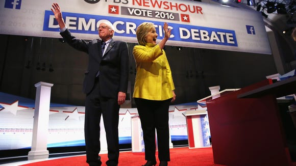 Bernie Sanders and Hillary Clinton walk out on stage for the PBS NewsHour Democratic debate.