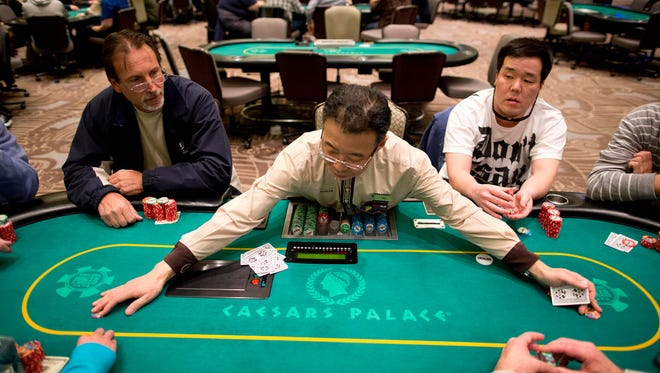 In this Feb. 27, 2013 file photo, dealer Han Kim, center, gathers up chips after a hand of Texas Hold 'em at a poker room in Caesar's Palace in Las Vegas.