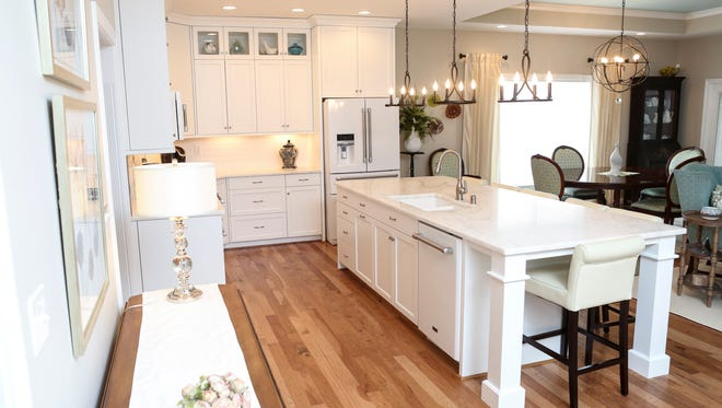 An overview of the kitchen area at the home of Ruby Leslie in eastern Jefferson County. There is an honed marble island with roll back chairs and white cabinets to the ceiling with glass inlays. Feb. 29, 2016