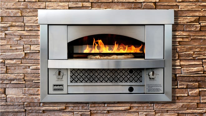 This Dec. 2014 photo provided by Kalamazoo Outdoor Gourmet shows the built-in Artisan Fire Pizza Oven that was released in 2015. Once it reaches 800°F, it can cook a Neapolitan-style pizza in fewer than three minutes. Pizza ovens for the kitchen or the backyard were one of the hot trends at this year's Kitchen and Bath Industry Show in Las Vegas.