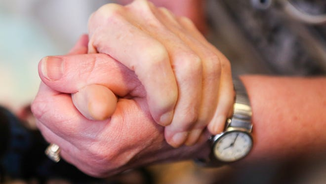 A hospice nurse holds the hand of an elderly patient.