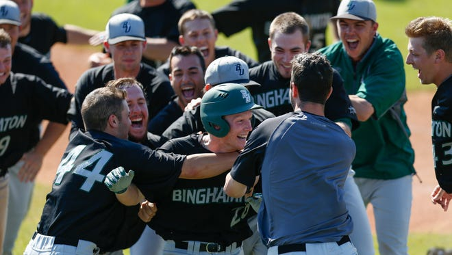 Binghamton players swarm Eddie Posavec after his bases-loaded single in the bottom of the 12th inning won the America East title for the Bearcats in the 2014 conference championship at LeLacheur Park in Lowell, Mass.
