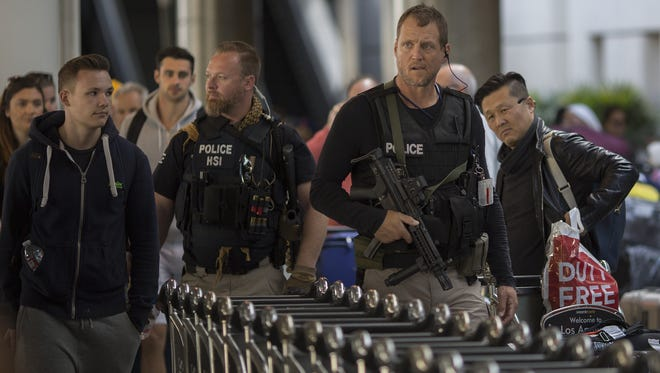 Homeland Security Investigations police patrol Tom Bradley International Terminal at LAX airport as security is heightened in reaction to bomb attacks in Brussels, Belgium March 22, 2016 in Los Angeles, Calif.