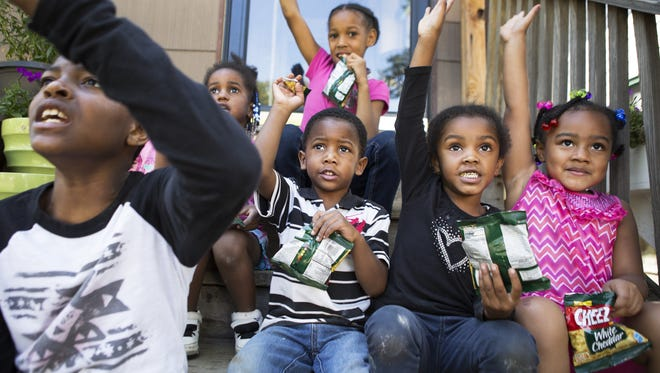 Joaquan Thomas Jr., 9, Javion Nelson, 3, Jamilah Lagree, 4, and Beautiful Sanford, 4, raise their hands in response to a question asked by Ronora James about snack time on Friday. James runs a child care business, Ora's Place Inc., out of her home.