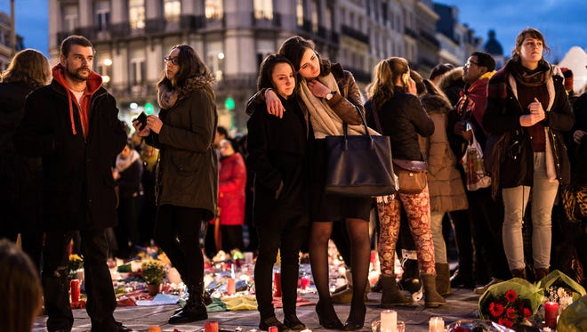 The Associated Press People gather Wednesday at a memorial site in Brussels. Belgian authorities were searching on Wednesday for a top suspect in the country?s deadliest attacks in decades. People gather at a memorial site located at the old stock exchange in Brussels on Wednesday, March 23, 2016. Belgian authorities were searching Wednesday for a top suspect in the country's deadliest attacks in decades, as the European Union's capital awoke under guard and with limited public transport after scores were killed or wounded in bombings on the Brussels airport and a subway station. (AP Photo/Valentin Bianchi)