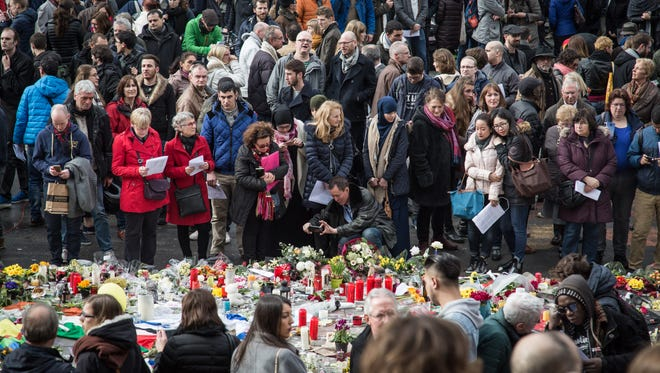 People gather at the makeshift memorial on Place de la Bourse square in Brussels to pay tribute to the victims of the Brussels terror attacks on March 25, 2016.