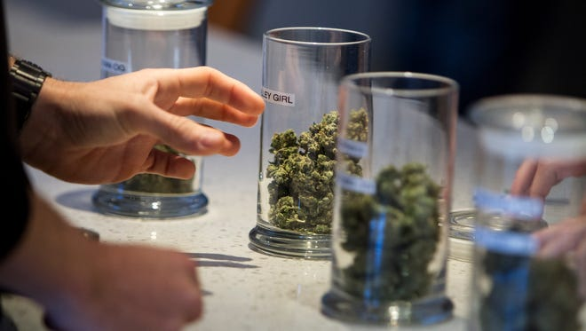 A customer looks at different strains of medical marijuana at TruMed Dispensary on Saturday, Apr. 2, 2016 in Phoenix. Zoning changes would make it more difficult for new dispensaries to set up in the city.