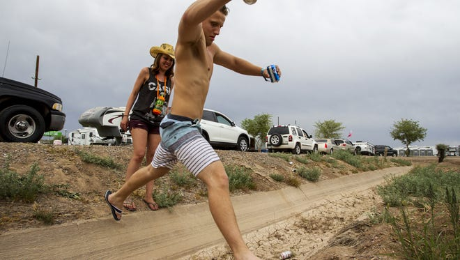 Michelle Block and Albrim Aliu jump over a ditch at a camping area  during Day 1 of Country Thunder Arizona on Thursday, April 7, 2016, in Florence.