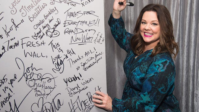 """Melissa McCarthy signs the wall at AOL Studios after participating in AOL's BUILD Speaker Series to discuss her new film """"The Boss"""" on Wednesday, April 6, 2016, in New York. (Photo by Charles Sykes/Invision/AP)"""