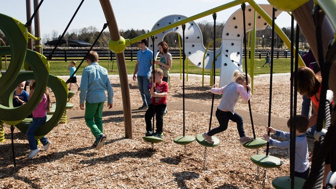 (center right) 3-year-old Ella Knight crosses a jungle gym as other children play on the newly opened Cliffside Playground at Broad Run Park.
