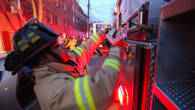 Wilmington firefighter Glenn Milton from Station 6 joins other firefighters at a residential fire at Madison and Eighth streets in 2013. Fire department overtime spending in 2015 has more than doubled what was spent in 2014 despite efforts to keep costs low.