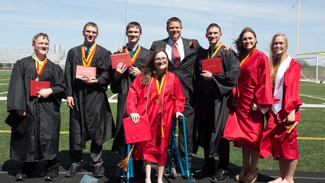 The McCaughey septuplets pose with their principal after graduating from Carlisle High School, Sunday, May 22, 2016. Pictured are: Nathan, left, Kenny Jr., Joel, Alexis, Principal Matthew Blackstone, Brandon, Kelsey, and Natalie.