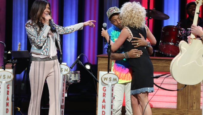 From left, artist Karen Fairchild of Little Big Town, artist Pharrell Williams, and artist Kimberly Schlapman of Little Big Town perform at the Grand Ole Opry on Tuesday, June 7, 2016, in Nashville, Tenn. (Photo by Laura Roberts/Invision/AP)
