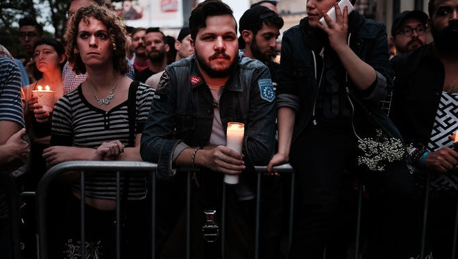Hundreds of people listen to speakers at a memorial gathering for those killed in Orlando in front of the iconic New York City gay and lesbian bar The Stonewall Inn on June 13, 2016.