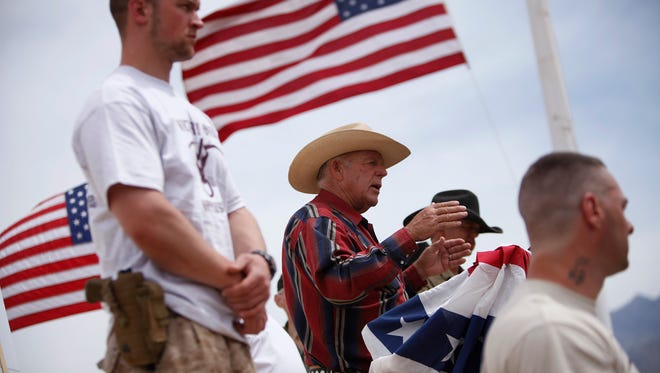 In this April 18, 2014. file photo, rancher Cliven Bundy, flanked by armed supporters, speaks at a protest camp near Bunkerville, Nev. Twelve of 19 defendants want separate trials in the federal criminal case involving cattleman Cliven Bundy and an armed standoff near his southern Nevada ranch. The state sovereignty figure and three of his sons are among those whose attorneys have filed documents in recent weeks seeking to sever their cases from the rest.