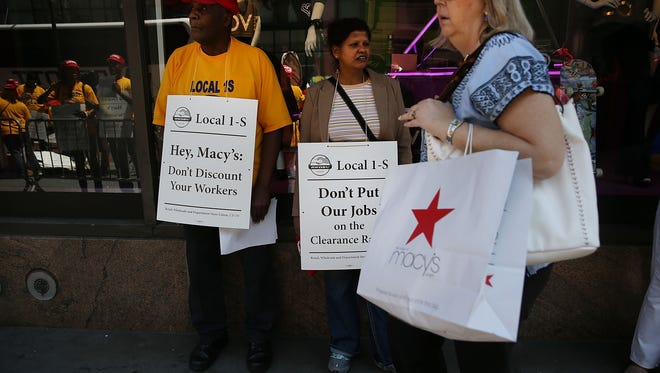 Shoppers walk by a demonstration of Macy's workers and other union activists outside of the retailer's flagship store at Herald Square in Manhattan on June 2, 2016 in New York City.