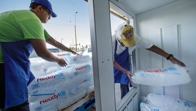 Luis Barraza and Roman Ortiz stock ice at the Food City along Van Buren and 27th Avenue Tuesday, June 21, 2016 in Phoenix,  Ariz.  The store is selling hundreds of bags of ice.