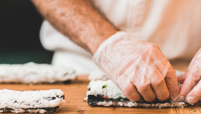 A chef prepares a roll of sushi.