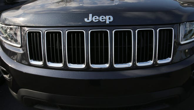 A 2015 Jeep Grand Cherokee vehicle is  seen on a sales lot.  Fiat Chrysler has announced that it is recalling more than 1.1 million cars and SUVs worldwide because the vehicles may roll away after drivers exit them.