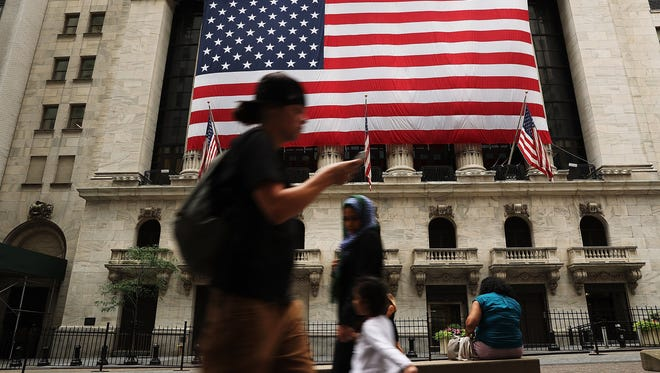 File photo shows passersby outside the New York Stock Exchange ini New York City on July 5, 2016.