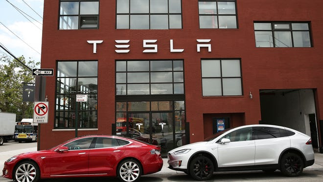 Tesla vehicles sit parked outside a new Tesla showroom and service center in Red Hook, Brooklyn on July 5, 2016 in New York City.