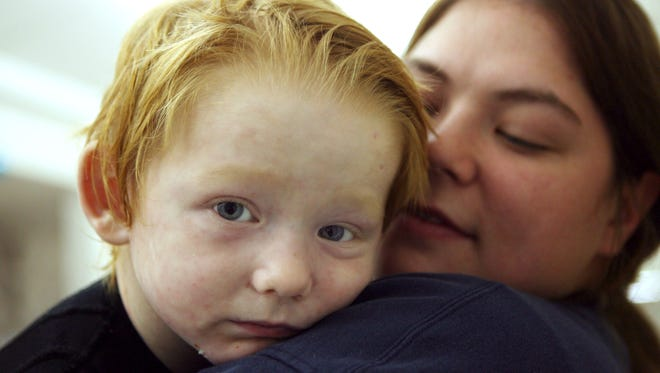 Austin Schoppert, 3, of Sioux Falls embraces his mother, Heather Coffee, as they wait to leave Shriner's Hospital, in Cincinnati on Dec. 24, 2009, to go home for the holidays.