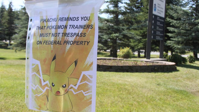 """This Tuesday, July 12, 2016, file photo, shows a sign at the National Weather Service in Anchorage, Alaska, informing """"Pokemon Go"""" players that it's illegal to trespass on federal property. The staff started noticing an uptick of people in the parking lot after the location was included as a gym in the popular game. The """"Pokemon Go"""" craze across the U.S. has people wandering into yards, driveways, cemeteries and even an off-limits police parking lot in search of cartoon monsters, prompting warnings that trespassers could get arrested or worse. (AP Photo/Mark Thiessen, File)"""