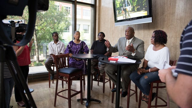 Paul Guy is joined by Rashad Dirton, Efia Nwangaza, Dianna Turner, mother of Deontea Mackey, and Tiffany Holliday at a press conference at City Hall on Monday, July 18, 2016.