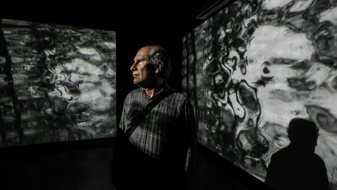 Louisville artist Julius Friedman poses in a multi-media installation that uses five projectors to show scenes of flowing water on multiple screens at the Frazier History Museum.  The installation is one of four original pieces that accompany more than 200 of Friedman's posters as a 50 year retrospective of his work.
