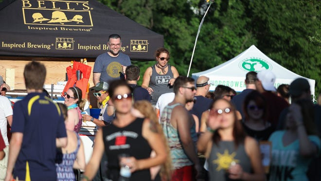 A heat wave did not stop large crowds from enjoying the MI Brewers Guild 19th Annual Summer Beer Festival at Riverside Park in Ypsilanti on Friday July 22, 2016.