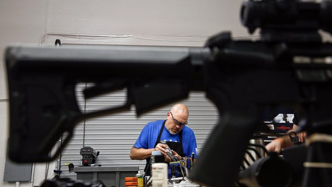 Jeff Coryell works on a rifle piece in the shop of his specialty firearms store and gunsmith shop, The Farm, in Naples on Friday, February 19, 2016.