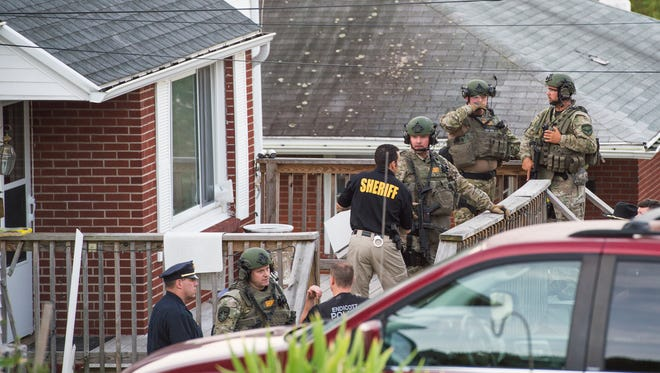Police stand outside a Pierce Avenue residence in Endwell as part of a drug trafficking investigation on July 28.