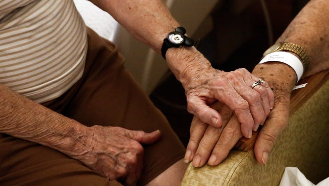 FILE - Jean Burnett, 91, holds the hand of Grant Haist, 93, while she visits with Haist at Avow Hospice in Naples on Tuesday, November 3, 2015. (Scott McIntyre/Staff)