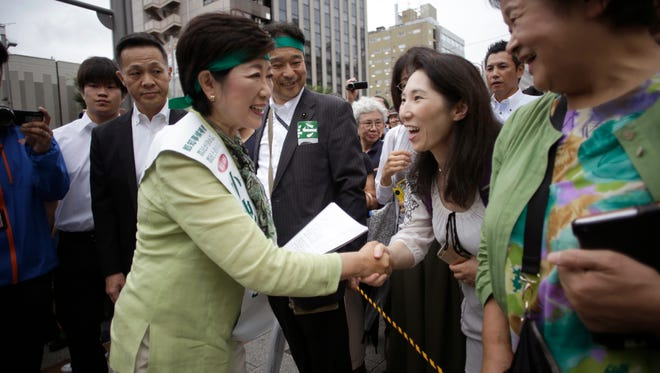 In this Friday, July 22, 2016 photo, former defense minister Yuriko Koike, left, shakes hands with a passerby during her campaign rally for the Tokyo gubernatorial election in Tokyo. Japan's capital with a population of more than 13 million people is voting Sunday, July 31, for its leader after two predecessors resigned over money scandals as Tokyo prepares to host the 2020 Olympics, and hopes to lead the nation in an economic turnaround.