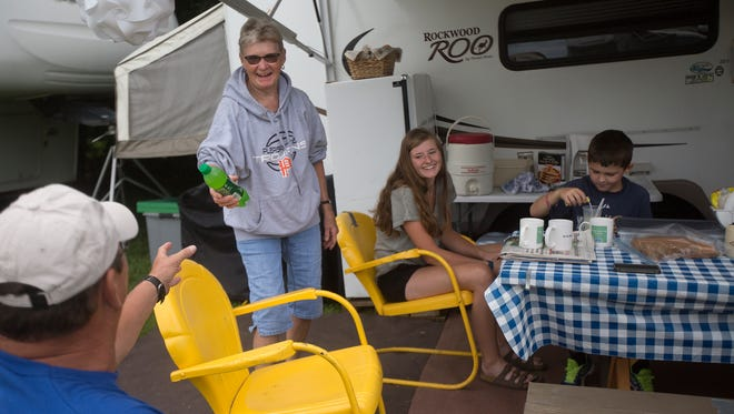 Linda Miller of Pleasantvile, left, hands a soda to Gary Wood of Corydon, while camping with Bailey Oliva, 18, and Stoney Wood, 7, both of Corydon, at Iowa State Fair campgrounds in Des Moines, Sunday, Aug. 7, 2016. The group has been camping at that site for 41 years. Miller recalled a time when they had no electric and no water available at the grounds.