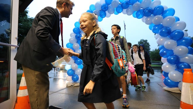 Sacred Heart Model School Principal Michael Bratcher greets students as they arrive at school.  Wednesday was the first day of classes for many area schools including area Catholic schools.August 17, 2016