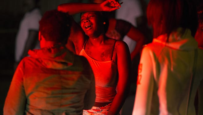 A young woman mourns at the scene of a shooting that left three dead and four injured on Genesee St., Aug. 20, 2015.