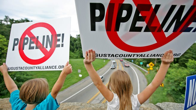 "Eleanor Cox, 5, left and her sister Maggie, 7, of Staunton chant ""NO PIPELINE"" with a crowd of people who turned out for Hands Across Our Land, a protest against the Atlantic Coast Pipeline staged at the stone bridge at the junction of Rt. 250 and the Blue Ridge Parkway in Afton on Thursday, August 18, 2016."