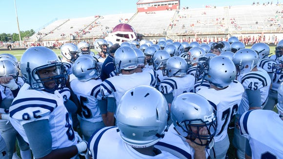 The Reitz Panther football team huddles up during warm-ups at Henderson's Colonel Stadium Friday. The Colonels host Reitz for the Hall of Fame game the first game of the season for both teams, August 19, 2016.