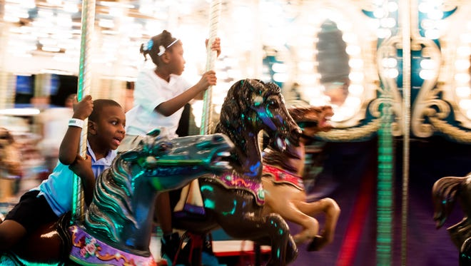 Two children go for a late-night cruise on the merry-go-round.