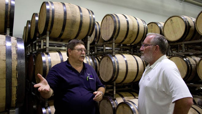 Spirits of French Lick owner John Doty, left, explained the distilling process to Alan Beck of Jasper. Beck received a sample of the new distillery's two-year bourbon which won't be available to the public for at least another 20 months.
