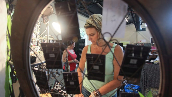 Jennifer Smith, left, and Laura Pope, right, set up jewelry displays during the last year's Art Fair at Mellwood.